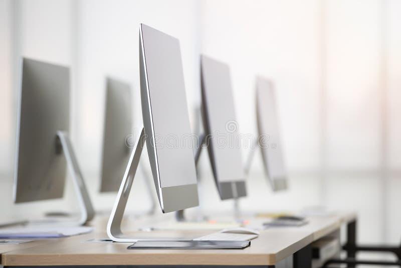 Группа в составе новые чистые компьютеры на столе в современном офисе с windo стоковые фотографии rf