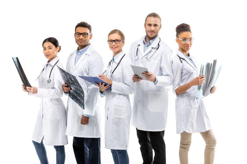 Группа в составе доктора детенышей усмехаясь профессиональные стоя совместно стоковая фотография rf