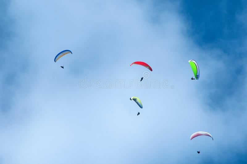 Группа в составе парапланы летая в голубое небо на фоне облаков Параглайдинг в небе на солнечный день стоковые изображения