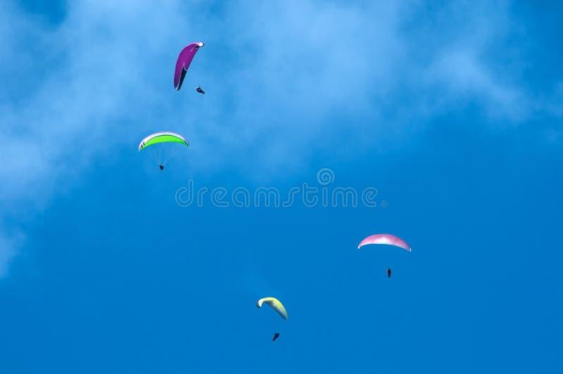 Группа в составе парапланы летая в голубое небо на фоне облаков Параглайдинг в небе на солнечный день стоковые фото