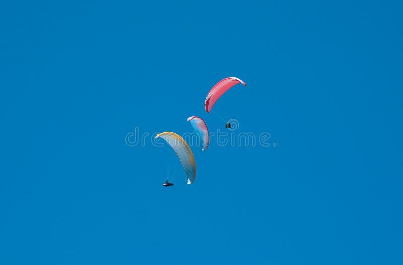Группа в составе парапланы летая в голубое небо на фоне облаков Параглайдинг в небе на солнечный день стоковая фотография