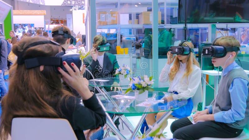 Группа в составе подростки используя шлемофон виртуальной реальности на выставке технологии стоковые фотографии rf