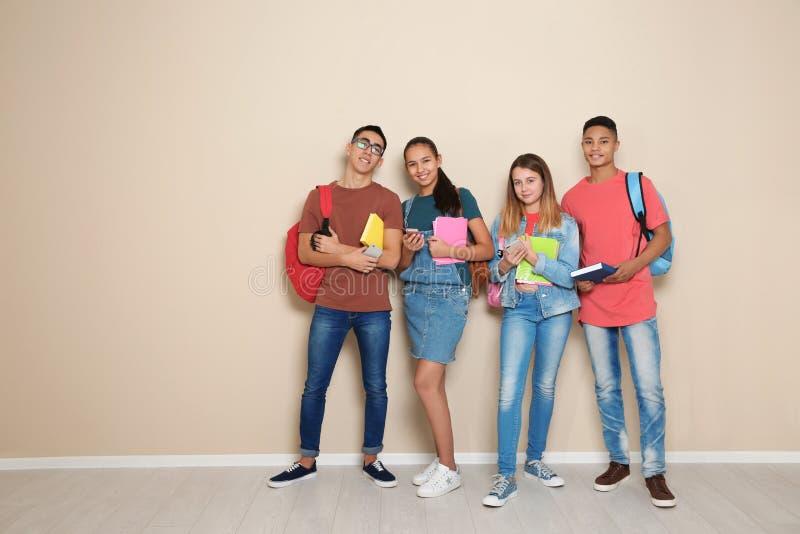 Группа в составе подростки против стены цвета стоковые фото
