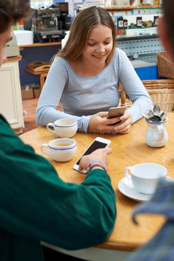 Группа в составе подростковые друзья встречая в кафе и используя мобильные телефоны стоковая фотография