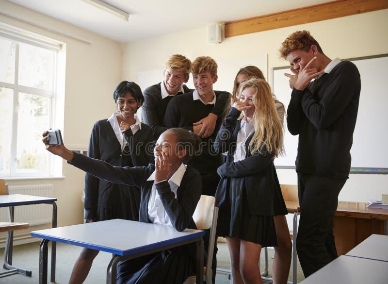 Группа в составе подростковые студенты представляя для Selfie в классе стоковое изображение rf