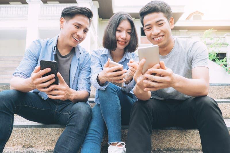 Группа в составе подросток используя мобильные телефоны стоковое изображение rf
