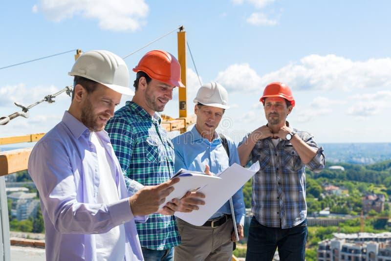 Группа в составе построители в защитных шлемах встречая на команде здания строительной площадки работая с сыгранностью инженера п стоковое фото