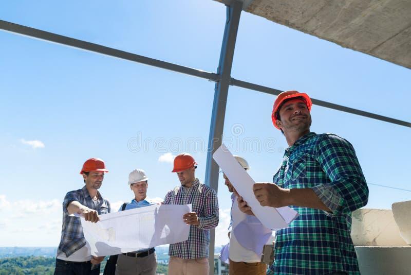 Группа в составе построители в плане владением защитного шлема обсуждая проект на строительной площадке работая совместно инженер стоковая фотография