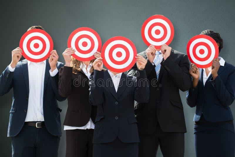 Группа в составе предприниматели пряча их стороны за Dartboard стоковая фотография rf