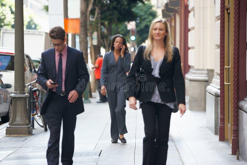 Группа в составе предприниматели идя вдоль улицы стоковое фото