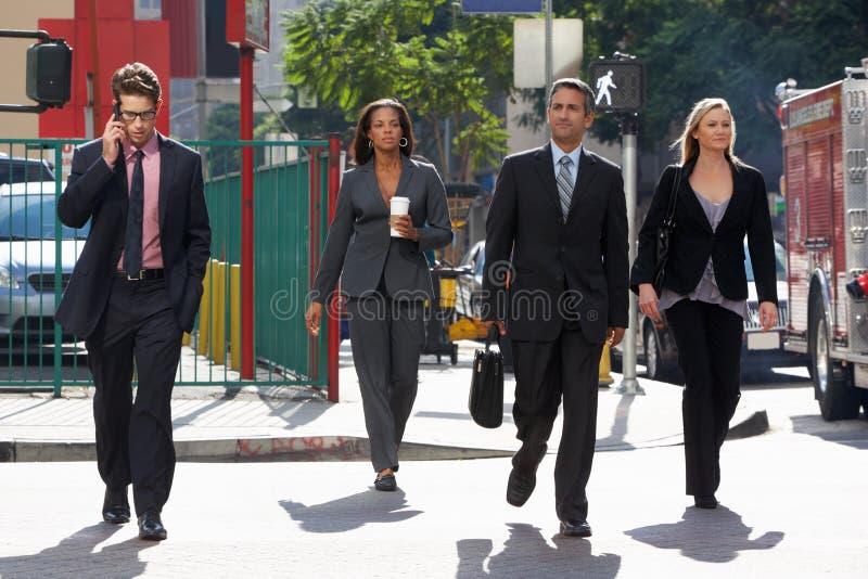 Группа в составе предприниматели пересекая улицу стоковые изображения
