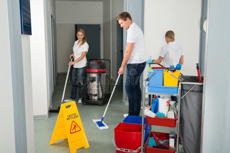 Группа в составе привратники очищая пол в коридоре стоковая фотография