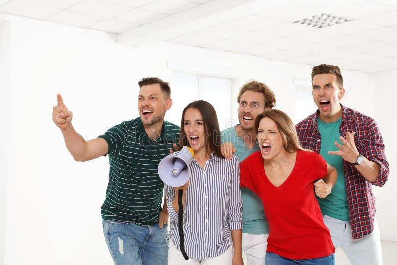 Группа в составе протестуя молодые люди с мегафоном стоковое фото