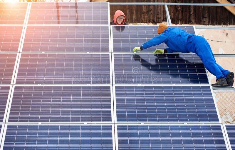 Группа в составе профессионалы устанавливая фотовольтайческие солнечные модули на верхней части крыши во время зимнего времени стоковая фотография