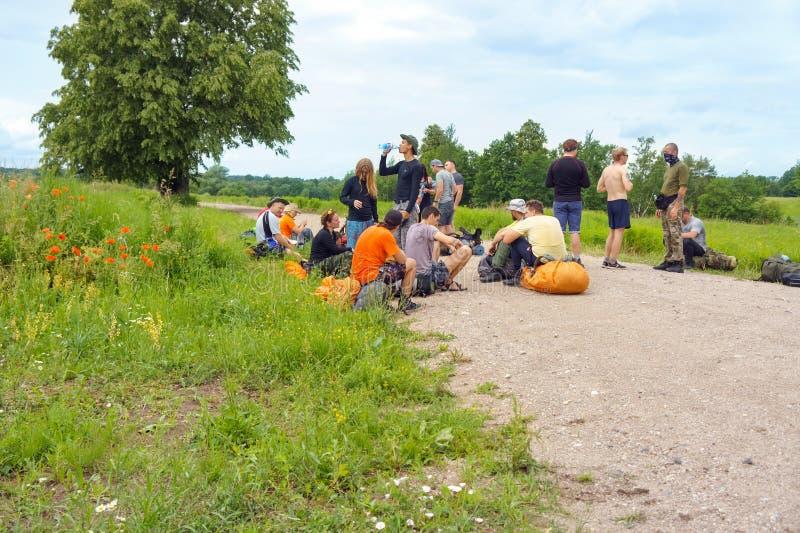 Группа в составе путешественники с большими рюкзаками, туристами ослабляет на дороге стоковые фото