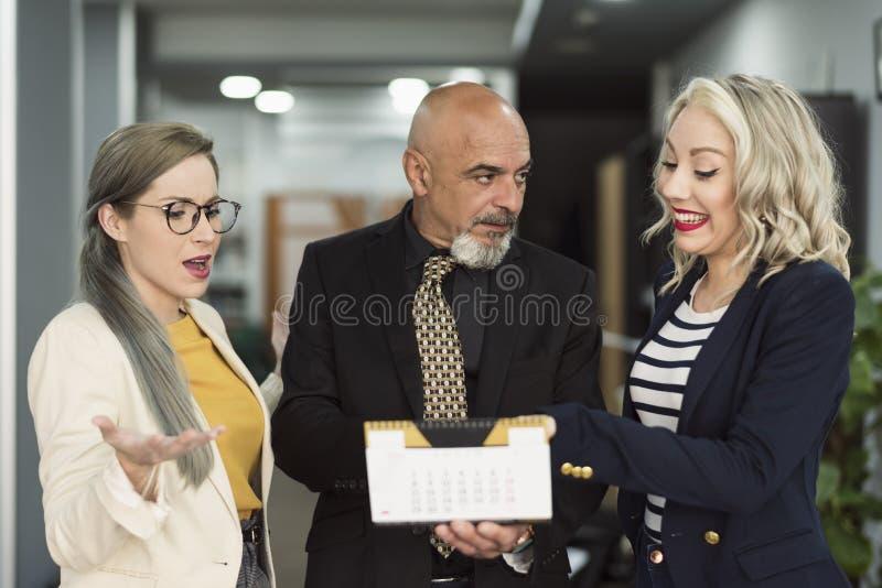 Группа в составе работники на офисе с выбором, каникулами или праздниками календаря стоковое изображение