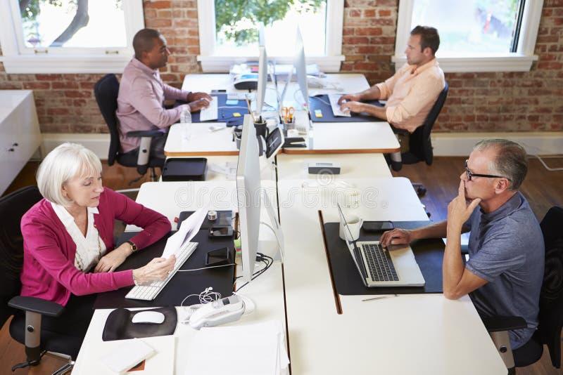 Группа в составе работники на столах в офисе современного дизайна стоковое фото
