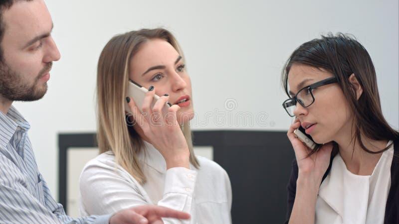 Группа в составе работники офиса общаясь с бумагами и телефонными звонками стоковое фото rf