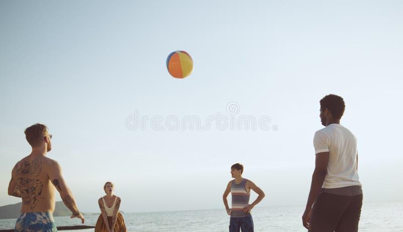 Группа в составе разнообразные друзья играя шарик пляжа совместно стоковые фотографии rf