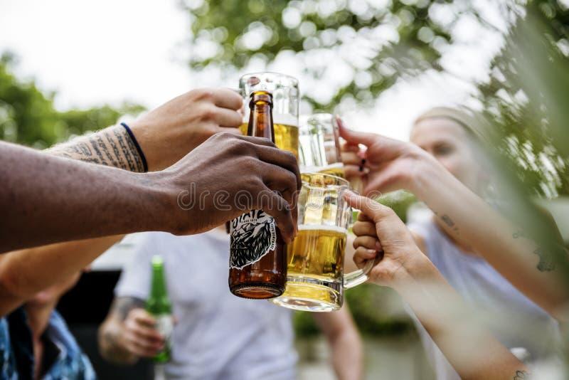 Группа в составе разнообразные друзья празднуя выпивая пив совместно стоковые фото