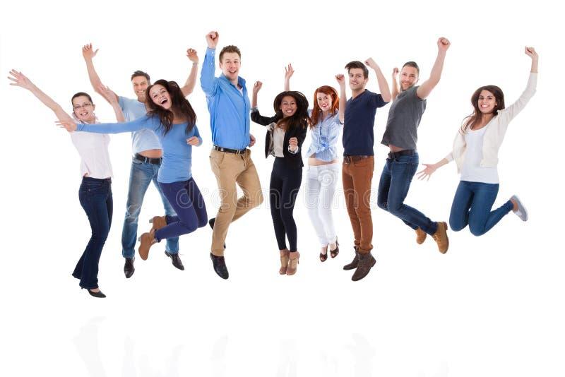 Группа в составе разнообразные люди поднимая оружия и скакать
