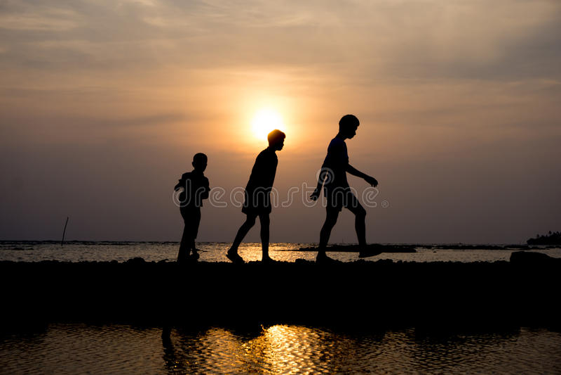 Группа в составе ребенок идя на заход солнца на пляже стоковая фотография rf