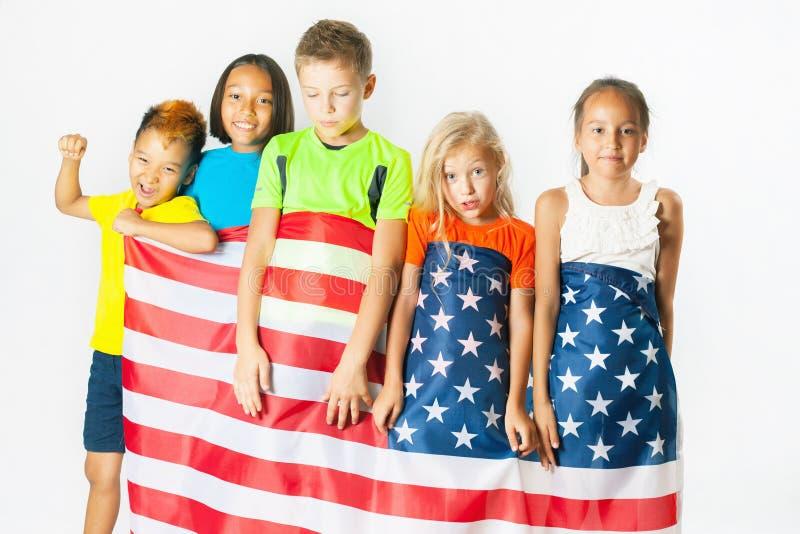 Группа в составе ребеята школьного возраста держа американский национальный флаг стоковая фотография rf