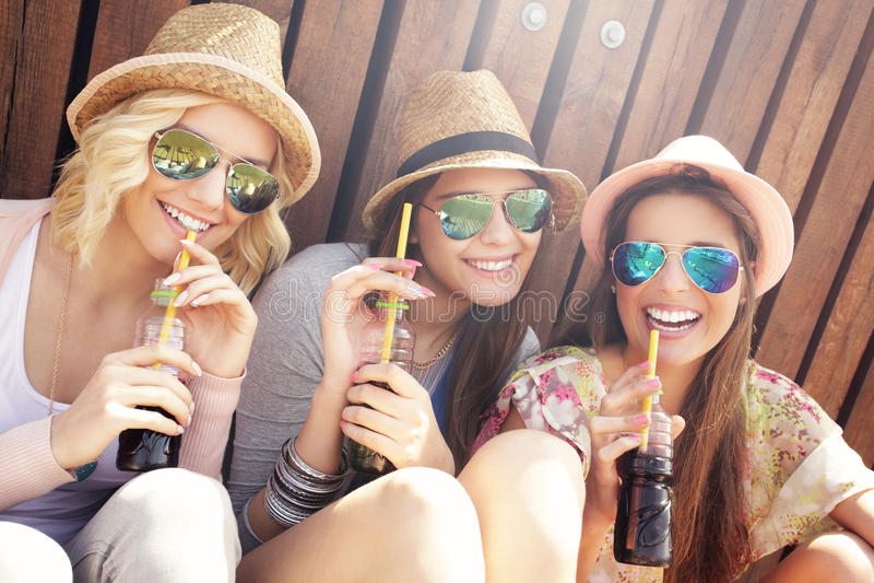 Группа в составе друзья выпивая коктеили в городе стоковая фотография