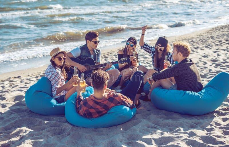 Группа в составе друзья выпивая на партии пляжа стоковое фото