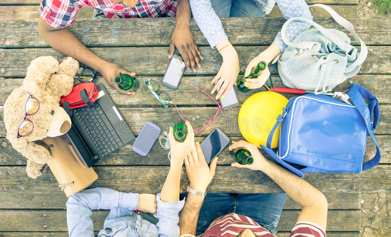 Группа в составе друзья выпивая пиво и используя передвижные умные телефоны стоковые изображения