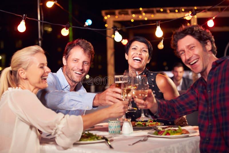 Группа в составе друзья есть обедающий на ресторане на крыше стоковое изображение