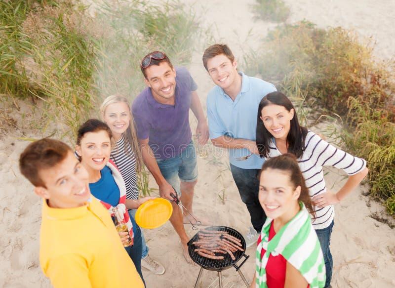 Группа в составе друзья делая барбекю на пляже стоковые изображения