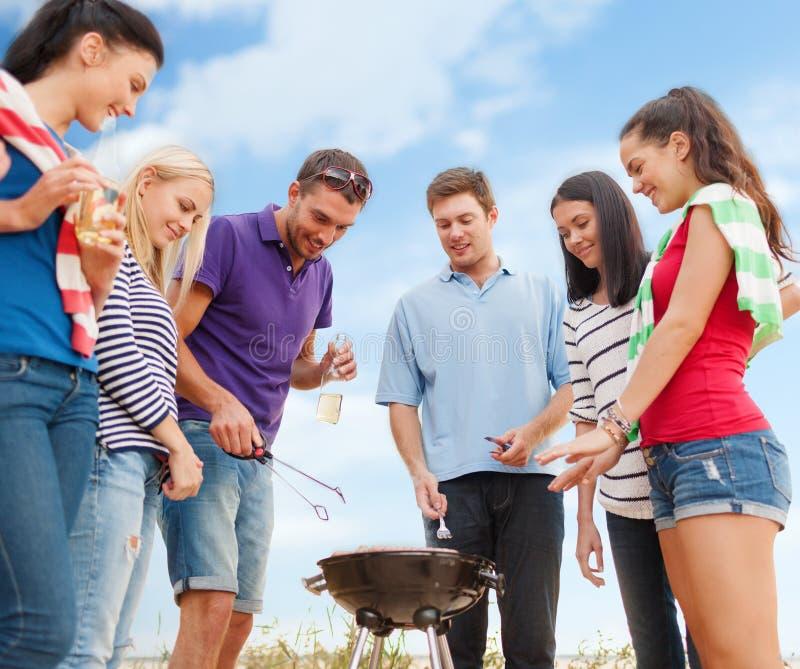 Группа в составе друзья делая барбекю на пляже стоковое фото rf