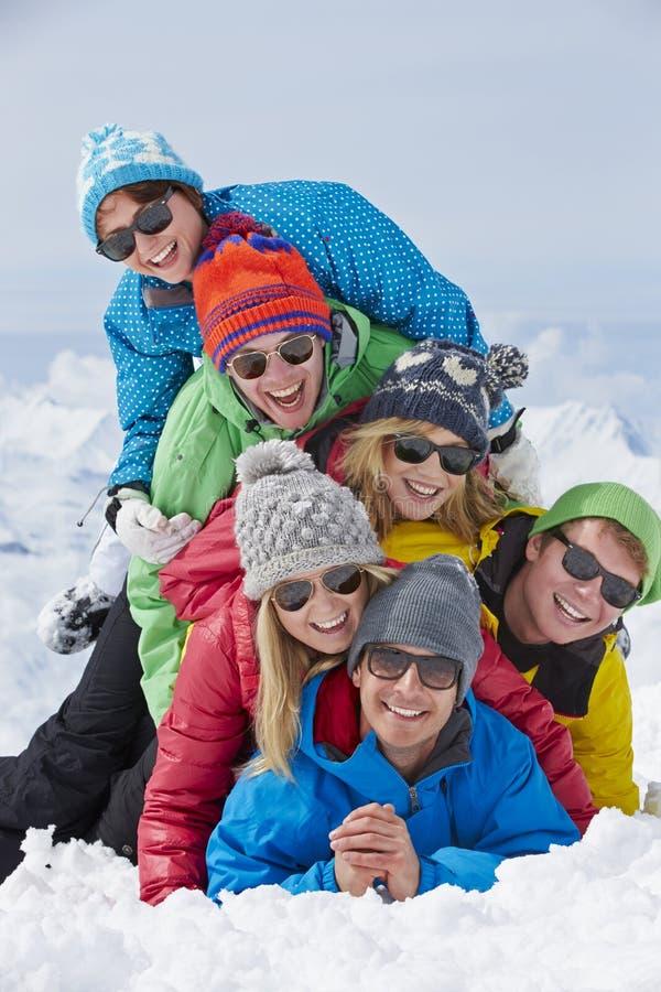 Группа в составе друзья имея потеху на празднике лыжи в горах стоковое фото rf