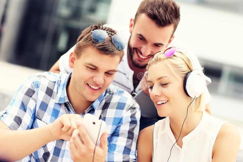Группа в составе друзья используя smartphones в кампусе стоковые изображения rf