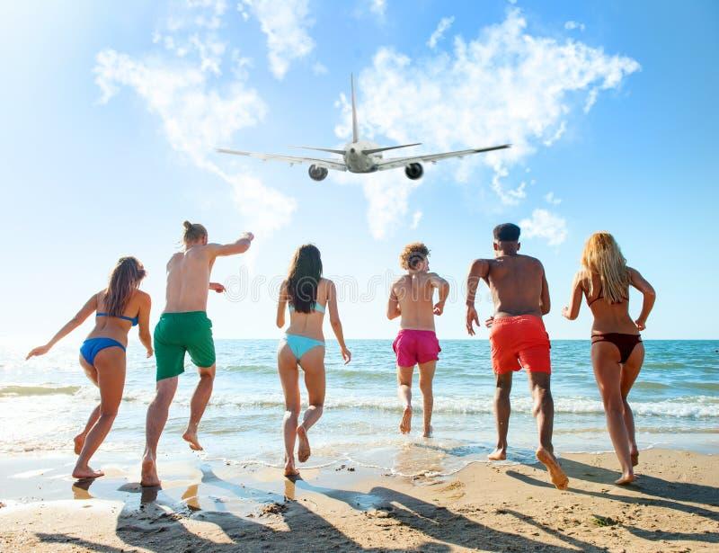 Группа в составе друзья, который побежали к морю с воздушным судном в небе Концепция перемещения и лета стоковые фото