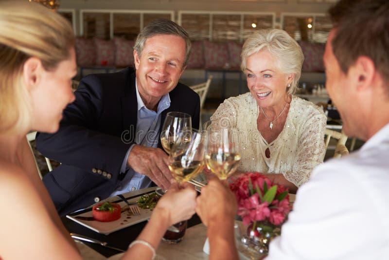 Группа в составе друзья наслаждаясь едой в ресторане стоковые фото