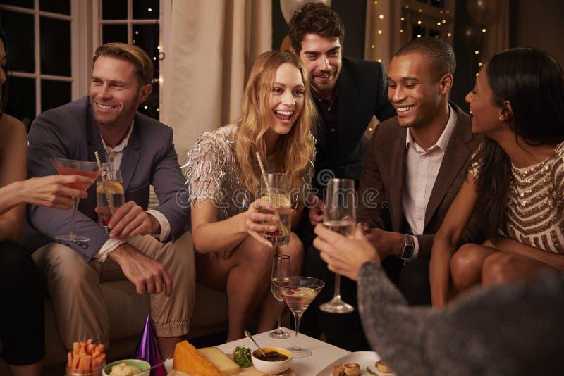 Группа в составе друзья наслаждаясь пить и закусками на партии стоковая фотография