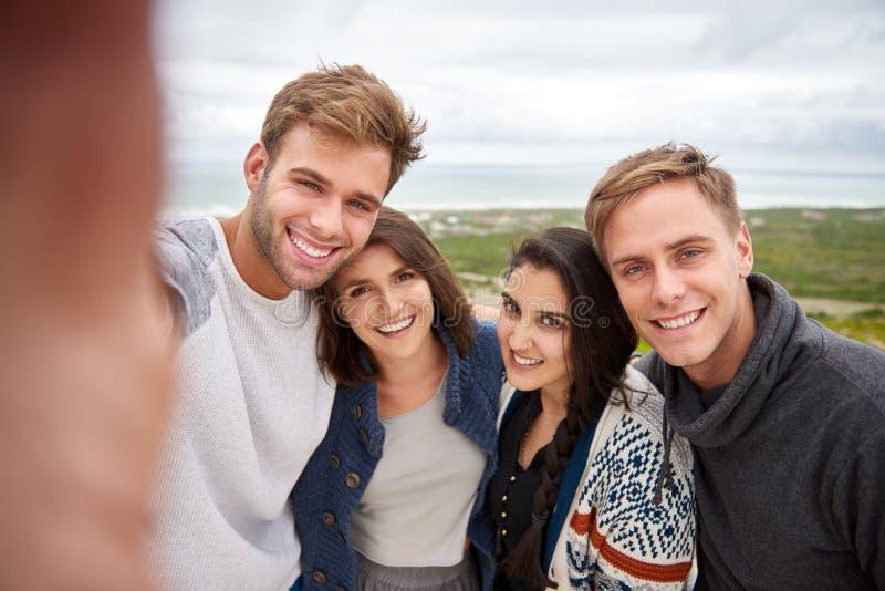 Группа в составе друзья принимая selfie outdoors в природу стоковое изображение