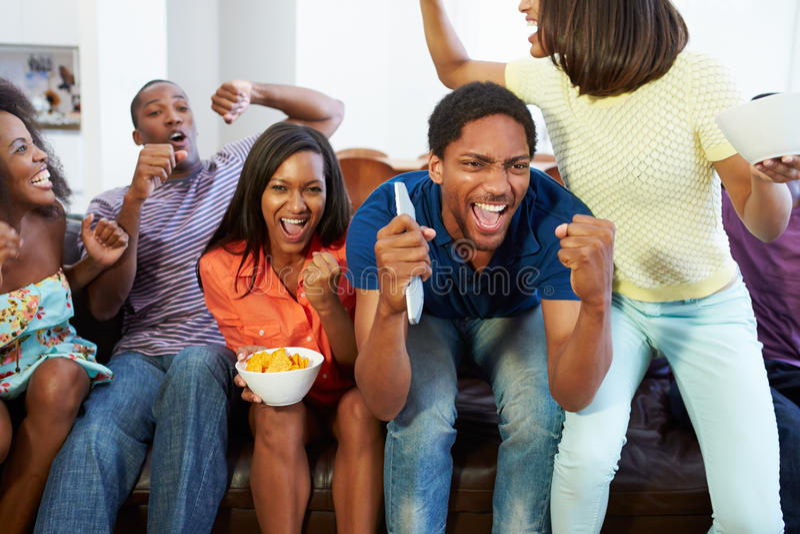 Группа в составе друзья сидя на софе смотря ТВ совместно стоковое изображение rf