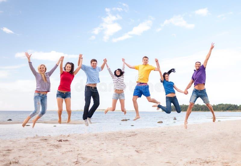 Группа в составе друзья скача на пляж стоковое фото