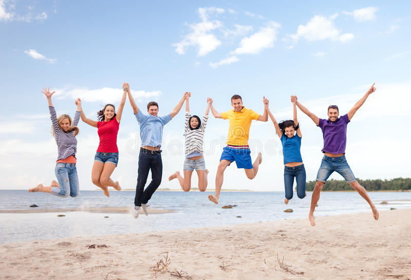 Группа в составе друзья скача на пляж стоковое изображение rf