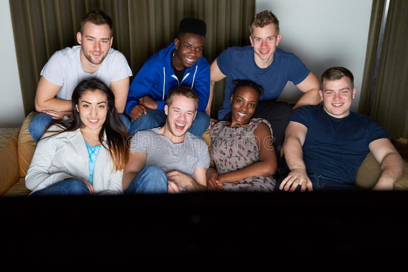 Группа в составе друзья смотря телевидение дома совместно стоковое изображение