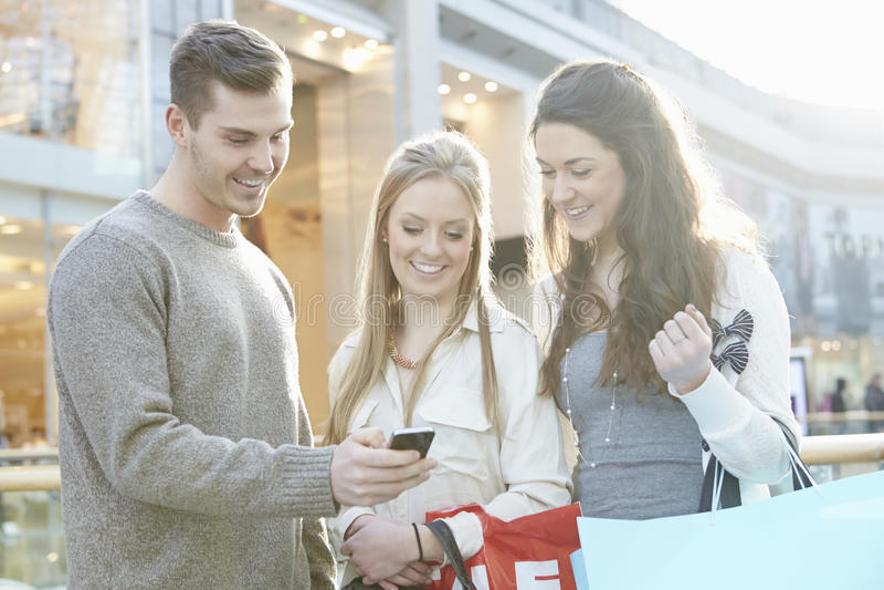 Группа в составе друзья ходя по магазинам в моле смотря мобильный телефон стоковое изображение