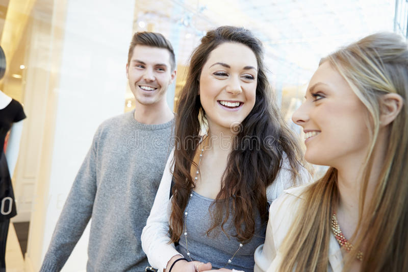 Группа в составе друзья ходя по магазинам в моле совместно стоковое фото rf