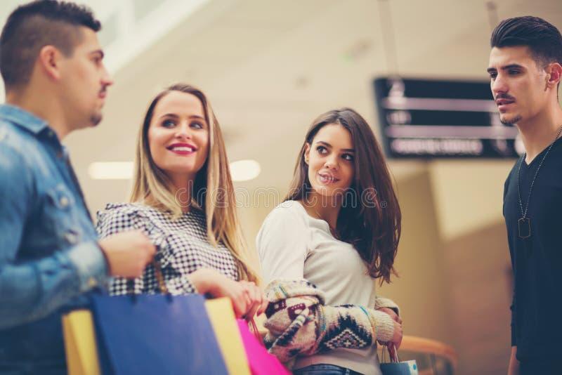Группа в составе друзья ходя по магазинам в моле совместно стоковая фотография