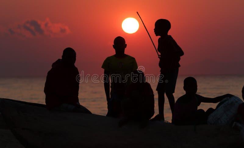 Группа в составе рыболовы и дети на восходе солнца, озеро Малави стоковые изображения rf