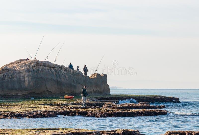 Группа в составе рыболовы удя в утре на береге моря стоковая фотография