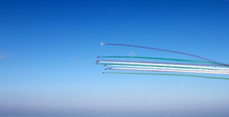 Группа в составе самолеты с покрашенным следом красным, белые, зеленые облака на предпосылке голубого неба, горизонтальном взгляд стоковая фотография