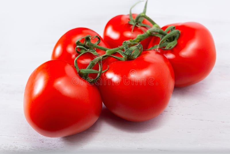 Группа в составе 5 свежее, зрелые красные томаты, все еще соединенные через зеленый стержень стоковая фотография rf